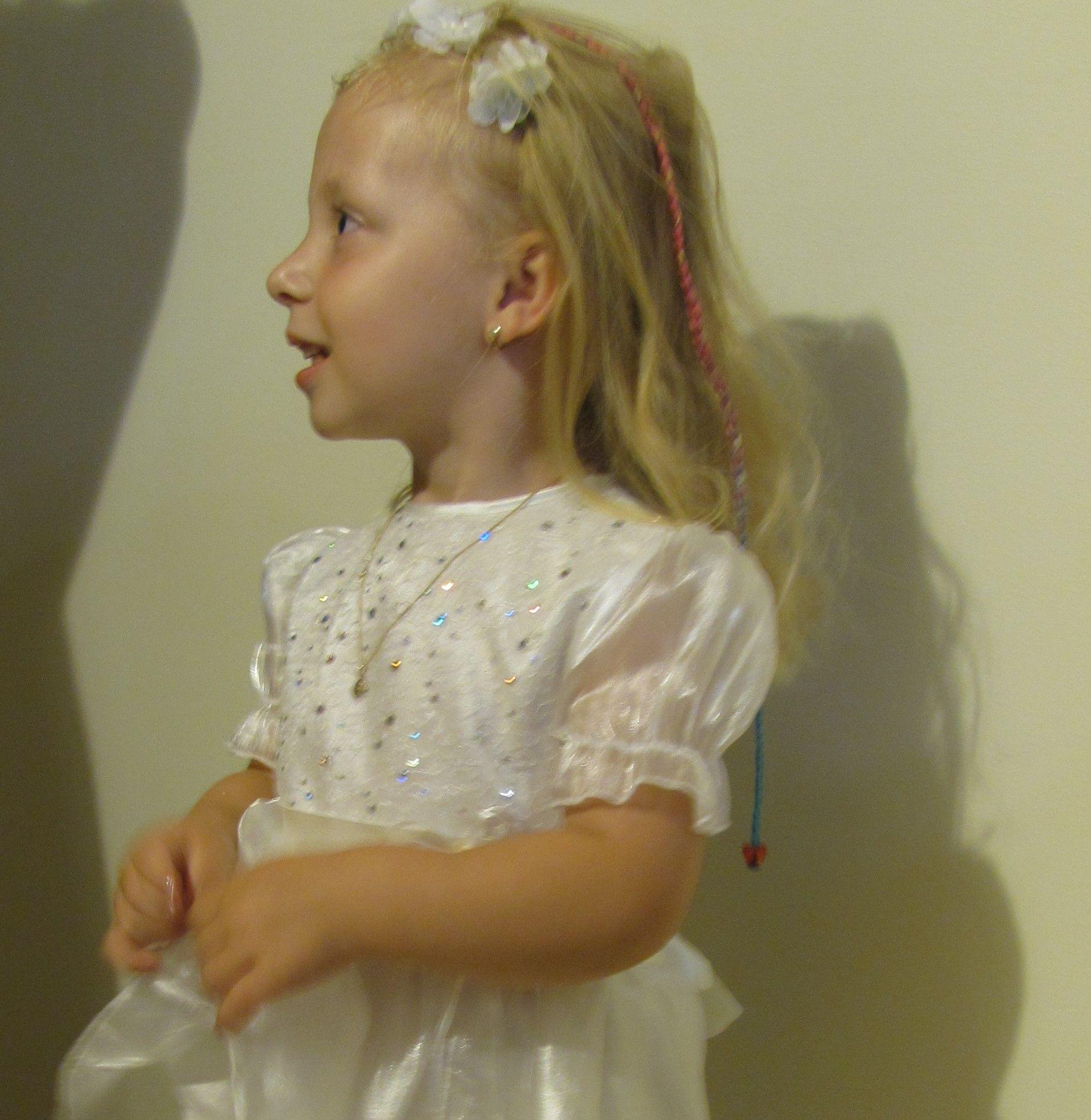 4-letnia dziewczynka ubrana w białą sukienkę po chrzcie św.