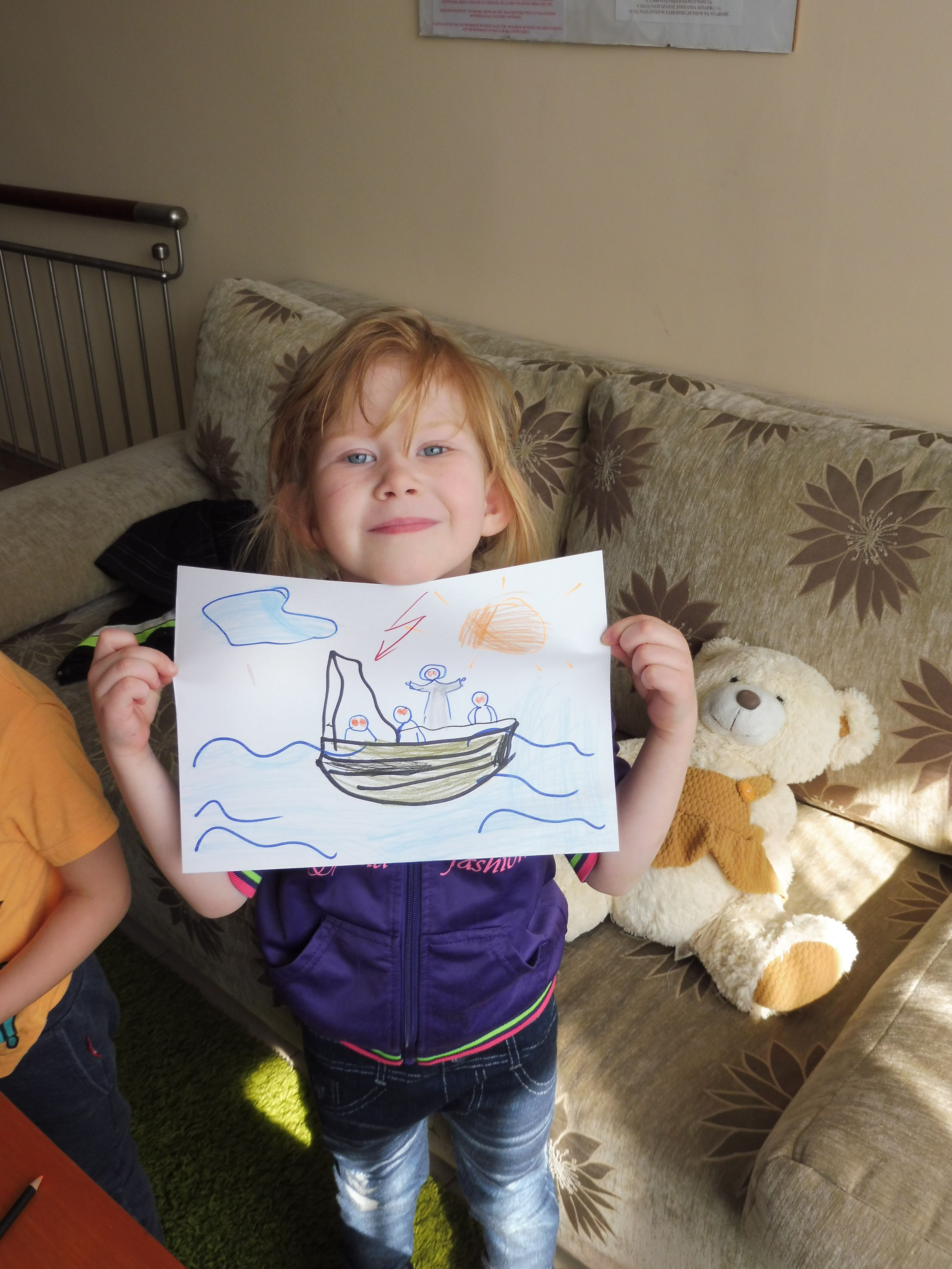 Dziewczynka trzymajaca pokolorowany obrazek perykopy o burzy na jeziorze
